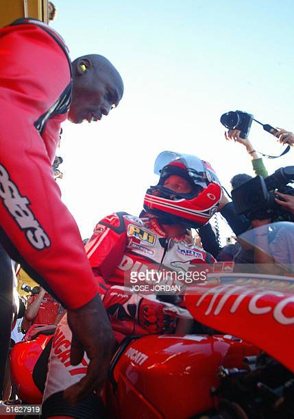 Basketball legend Michael Jordan chats with countryman Randy Mamola during the Spanish Motorcycle Grand Prix at the Ricardo Tormo racetrack in...