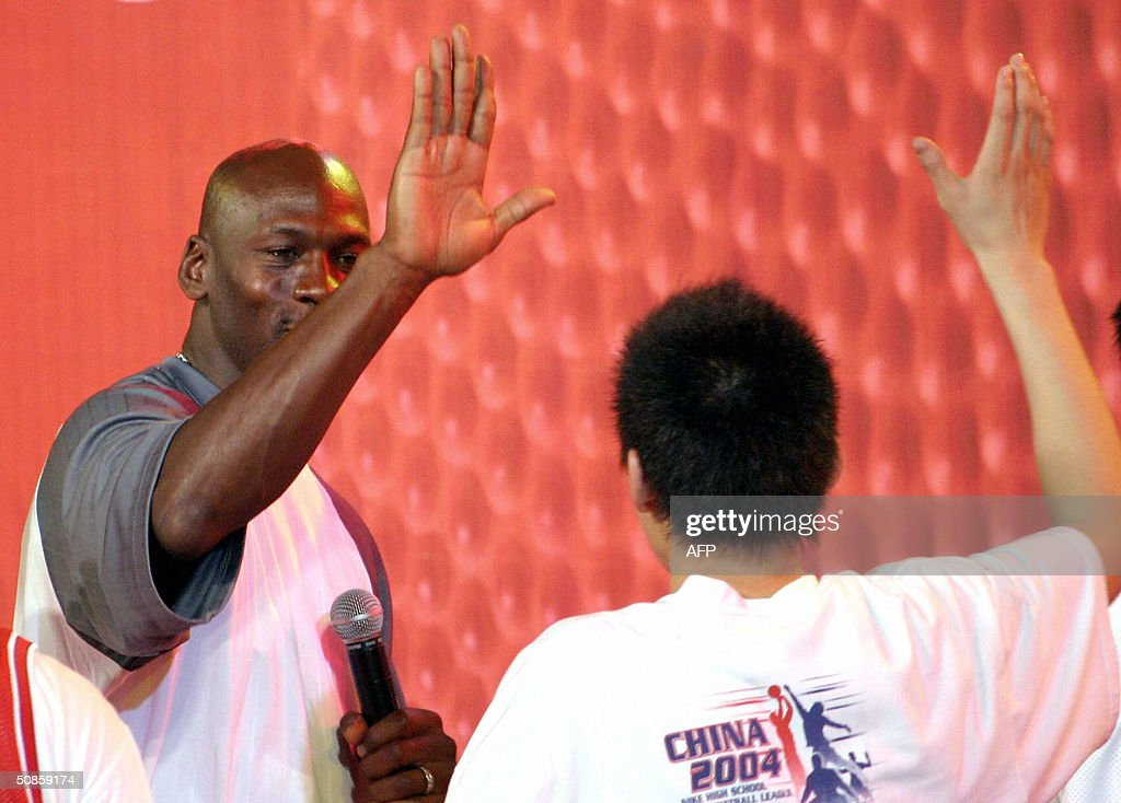 US basketball legend Michael Jordan high-fives a high-school player from the title winning Shenyang #31 High School team, 20 May 2004, during a trophy presentation following China's high school championships at the Worker's Stadium Gymnasium in Beijing. Despite being a no show at open public events in the Chinese capital yesterday, Jordan's slick promotional tour has grabbed more headlines than the return to China of the nation's homegrown NBA hero Yao Ming.