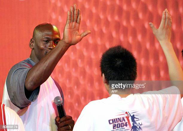 US basketball legend Michael Jordan highfives a highschool player from the title winning Shenyang High School team 20 May 2004 during a trophy...