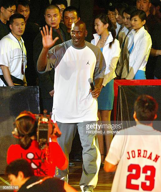 US basketball legend Michael Jordan waves to the crowd as he arrives for a presentation ceremony for China's High School championship 20 May 2004 at...