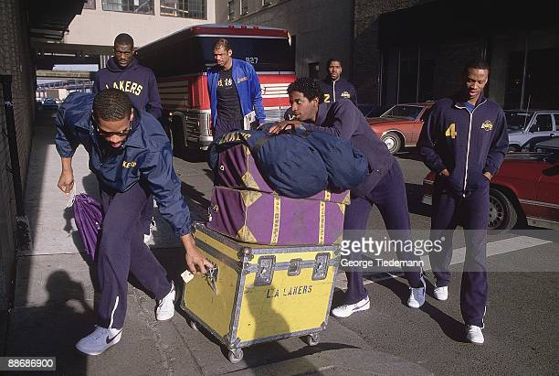 Los Angeles Lakers Larry Spriggs and AC Green push equipment while Michael Cooper Kareem AbdulJabbar Magic Johnson and Byron Scott watch before...