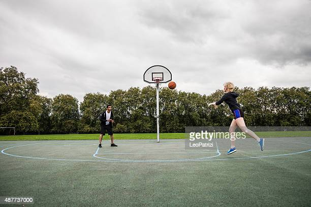 basketball man-woman playing in a london playground - passing sport stock pictures, royalty-free photos & images