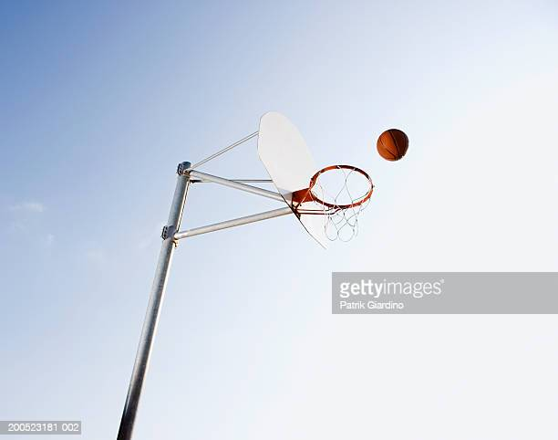 basketball mid-air to hoop outdoors, low angle view - basketball hoop stock pictures, royalty-free photos & images