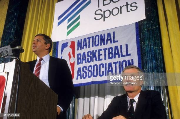 NBA commissioner David Stern at podium with Ted Turner sitting beside him during press conference announcing Rick Barry and Bill Russell as the new...