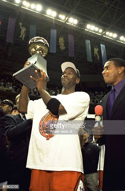 Basketball NBA Finals Chicago Bulls Michael Jordan victorious with sixth NBA Championship trophy and NBC Sports media announcer Ahmad Rashad after...