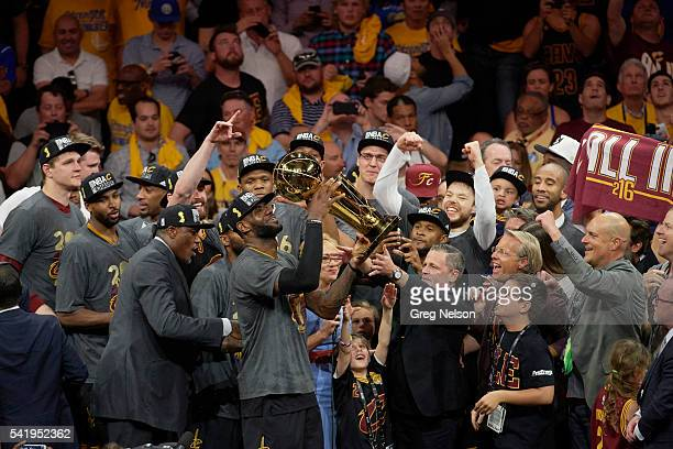 NBA Finals Cleveland Cavaliers LeBron James victorious holding up Larry O'Brien trophy with owner Dan Gilbert after winning series vs Golden State...