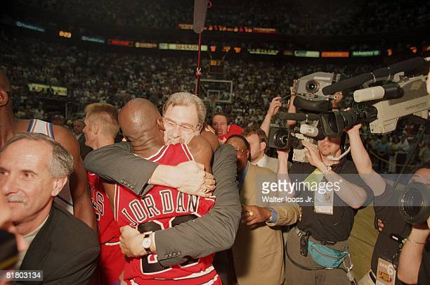 Basketball NBA finals Closeup of Chicago Bulls coach Phil Jackson and Michael Jordan surrounded by media victorious hugging after winning game vs...