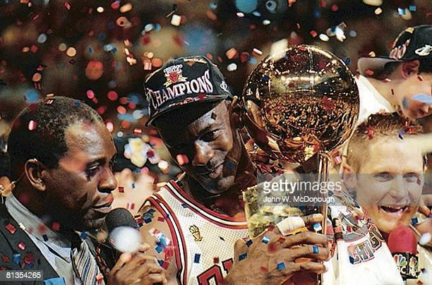 Basketball NBA Finals Closeup of Chicago Bulls Michael Jordan and Steve Kerr victorious with NBA Championship trophy and media announcer after...