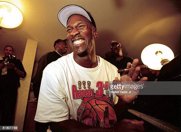 Basketball NBA Finals Closeup of Chicago Bulls Michael Jordan victorious playing piano and smoking cigar in hotel after winning Game 6 and...