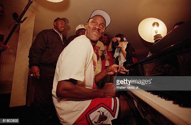 Basketball NBA finals Closeup of Chicago Bulls Michael Jordan victorious playing piano and smoking cigar in hotel after winning game and championship...