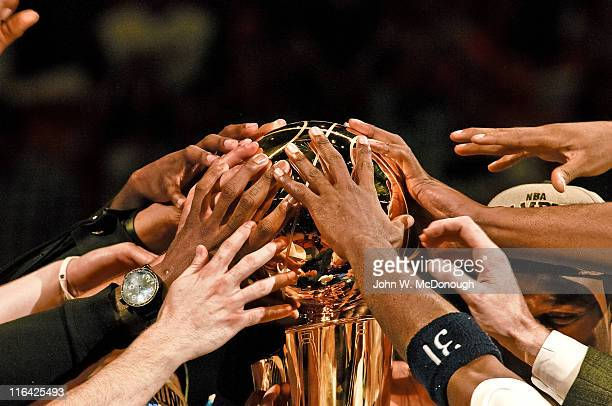 NBA Finals Closeup view of hands of Dallas Mavericks players victorious touching Larry O'Brien trophy after winning Game 6 and championship series vs...