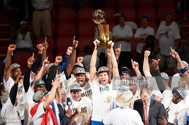NBA Finals Dallas Mavericks Dirk Nowitzki victorious holding Larry O'Brien Championship trophy with teammates after winning Game 6 and championship...