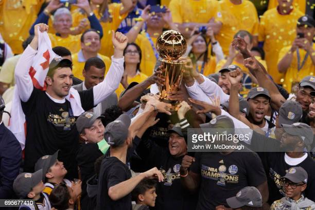 NBA Finals Golden State Warriors owner and CEO Joe Lacob and owner Peter Guber victorious holding up Larry O'Briend NBA Championship trophy with...