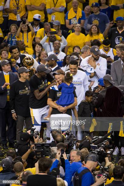 NBA Finals Golden State Warriors Stephen Curry victorious holding daughter Riley after winning series vs Cleveland Cavaliers at Oracle Arena Game 5...