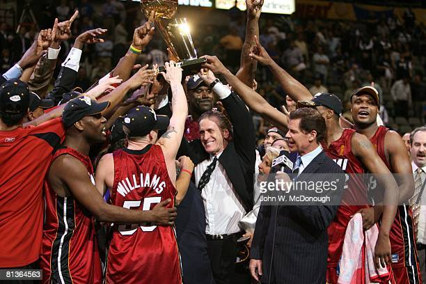 Basketball: NBA Finals, Miami Heat head coach Pat Riley victorious with Larry O'Brien Trophy and team after winning game and championship vs Dallas...