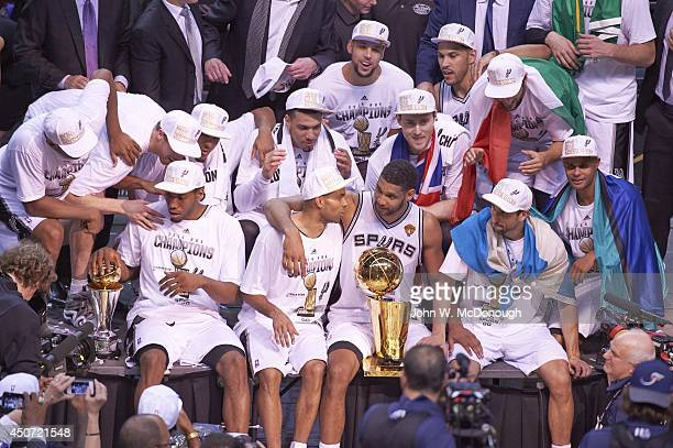 NBA Finals San Antonio Spurs Tim Duncan with Larry O'Brien trophy with arm around Tony Paker and Kawhi Leonard with MVP trophy surrounded by...