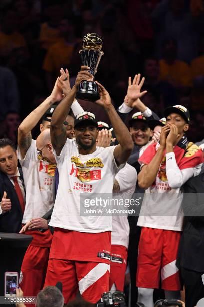 NBA Finals Toronto Raptors Kawhi Leonard victorious holding up NBA Finals MVP Trophy with teammates after winning game vs Golden State Warriors at...