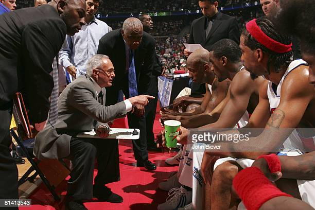 Basketball NBA playoffs Detroit Pistons coach Larry Brown on sidelines talking with team on bench during timeout vs Miami Heat Auburn Hills MI...