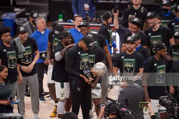 Playoffs: Milwaukee Bucks Giannis Antetokounmpo , holding and looking down at Eastern Conference Championship Trophy with teammates after winning...