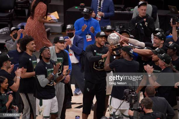 Playoffs: Milwaukee Bucks Giannis Antetokounmpo victorious, holding Eastern Conference Championship Trophy with teammates after winning game and...