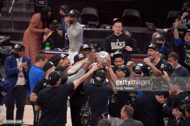 Playoffs: Milwaukee Bucks players reaching for and touching Eastern Conference Championship Trophy after winning game and series vs Atlanta Hawks at...