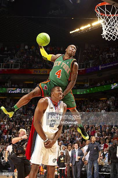 NBA Slam Dunk Contest New York Knicks Nate Robinson in action leaping over Orlando Magic Dwight Howard during finals on AllStar Saturday Night of All...