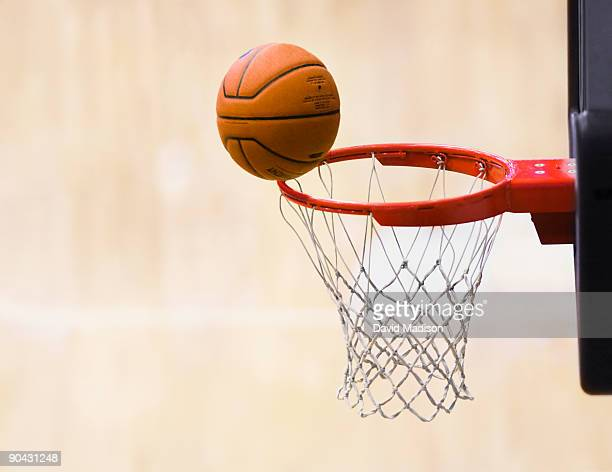 Basketball on rim of basket.