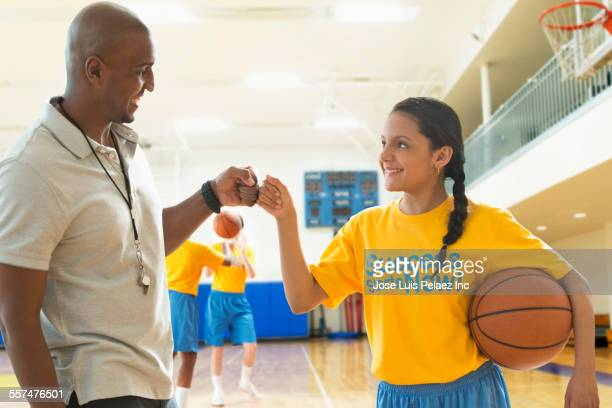 basketball player and coach fist-bumping during practice - puerto rican ethnicity stock pictures, royalty-free photos & images