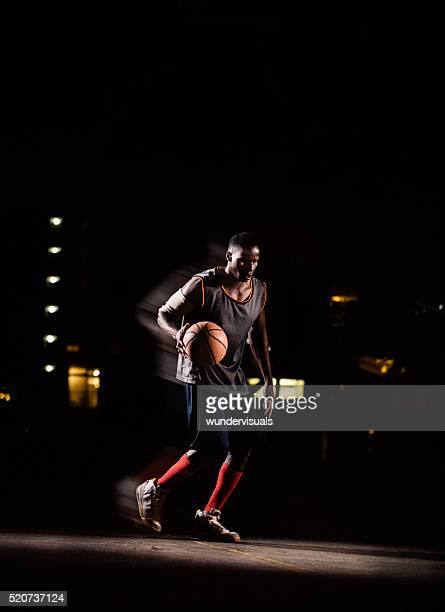 Basketball Player Bouncing Ball on Court in Night
