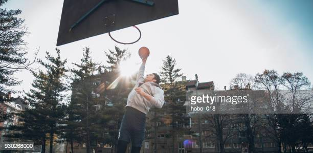 basketball player doing slam dunk - shooting baskets stock photos and pictures