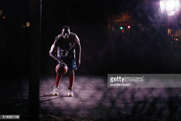 Basketball Player Dribbling Ball on Court in Night