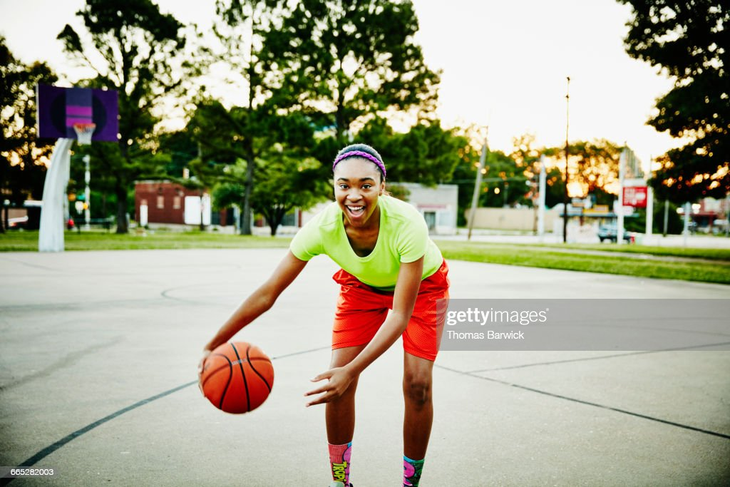 Basketball player dribbling ball on outdoor court : Stock Photo