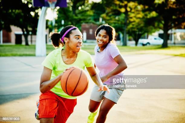 Basketball player dribbling ball past defender
