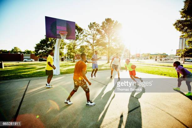 basketball player dribbling ball past defender - leanincollection stock pictures, royalty-free photos & images