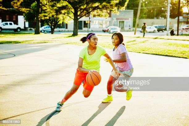 Basketball player dribbling ball past defender