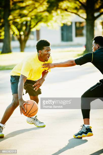 basketball player dribbling ball past defender - blocking sports activity stock pictures, royalty-free photos & images
