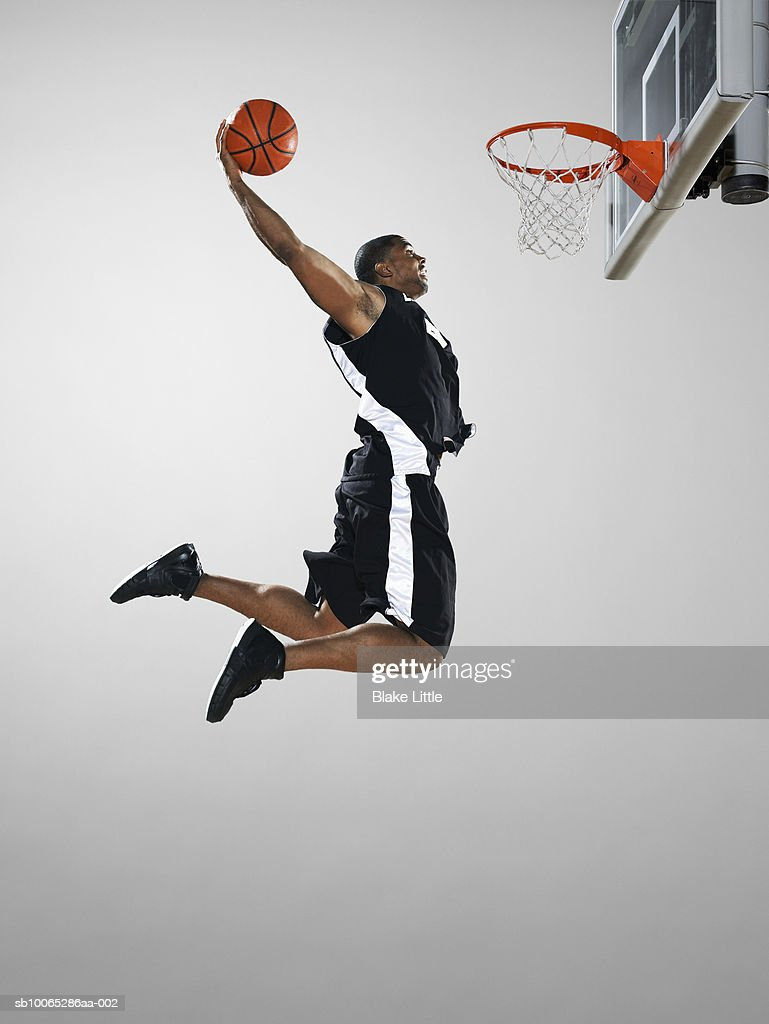 Basketball player dunking ball, low angle view : Foto stock