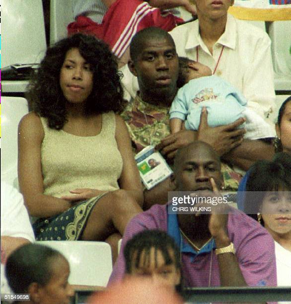 S basketball player Earvin Magic Johnson holds his son Earvin Johnson III while watching the US women's basketball team play Spain 03 August 1992 in...