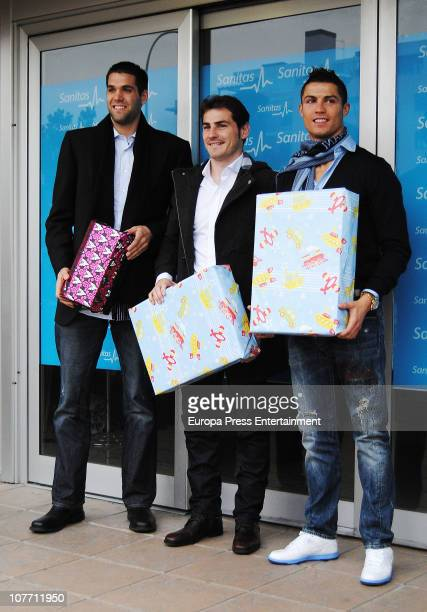 Basketball player Felipe Reyes and football players Iker Casillas and Cristiano Ronaldo hand out toys to children at Sanitas Hospital on December 20...