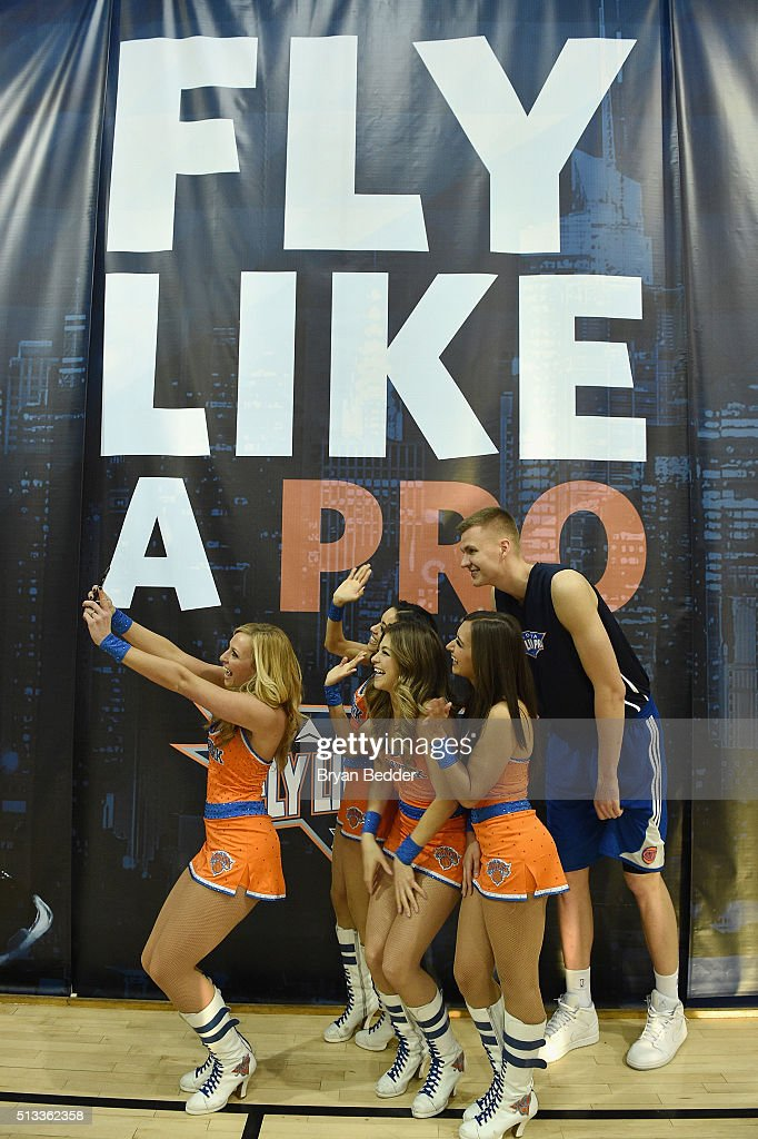 NBA basketball player for the New York Knicks, Kristaps Porzingis (R) celebrates Delta Air Lines Fly Like a Pro campaign with a H-O-R-S-E competition at Chelsea Piers in New York City on March 2, 2016.