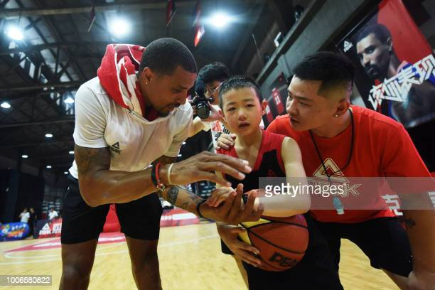 US basketball player George Hill talks to a boy during a training session at a basketball camp in Hangzhou in China's eastern Zhejiang province on...