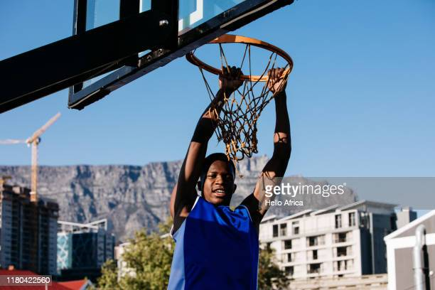 Basketball player happily hanging on hoop after scoring