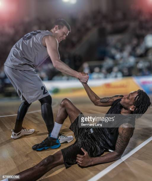 basketball player helping up his oponent - fair play sport foto e immagini stock