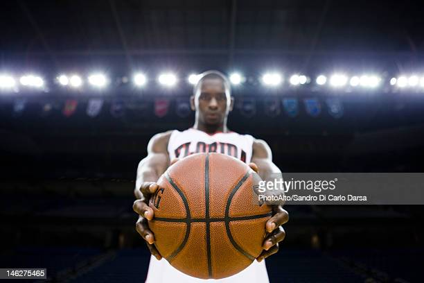 Basketball player holding basketball, focus on foreground