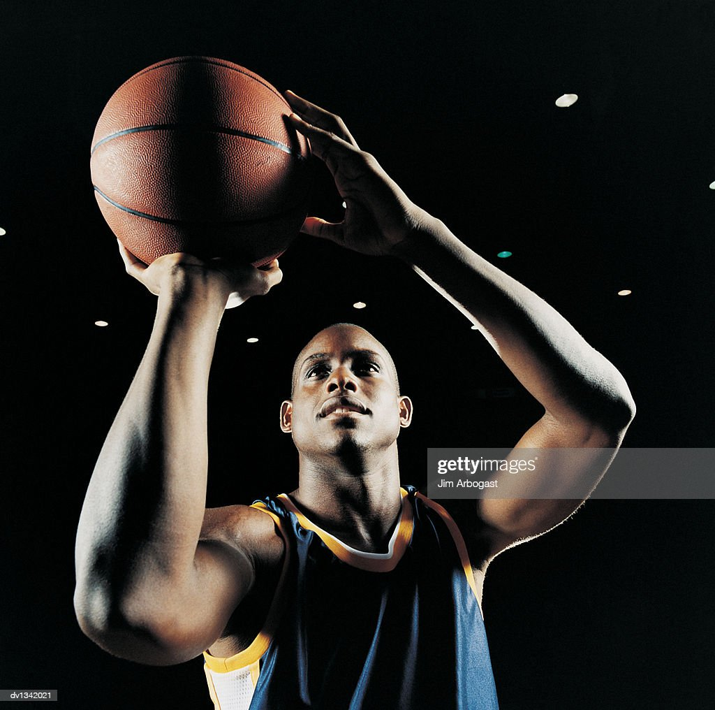 Basketball Player Holding the Ball and Looking Up to Aim : ストックフォト