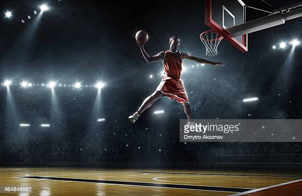 A basketball player in midair about to slam dunk a ball