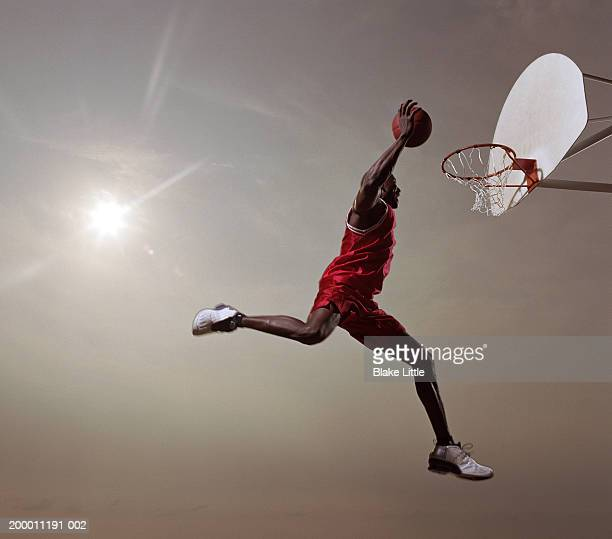 basketball player in mid-air jump, about to slam dunk basketball - shooting baskets stock pictures, royalty-free photos & images