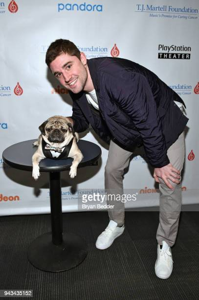 Basketball player Joe Harris of the Brooklyn Nets poses with Doug the Pug during TJ Martell Foundation's 17th Annual New York Family Day at...