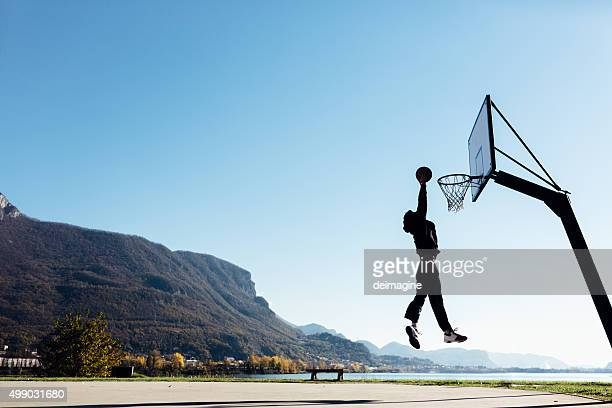 Basketball player jumping and placing ball in the hoop