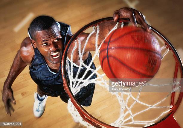 basketball player jumping below basket, elevated view (enhancement) - shooting baskets stock photos and pictures